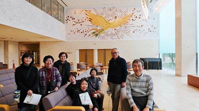 "Against the relief of ""Phoenix fire birds"" soaring to the future  From left to right: Ms. Niki, Ms. Watanabe, Ms. Matsuno, Ms. Miho, Ms. Kurumaji, Ms. Taguchi, Mr. Takahashi, Mr. Tachibana"